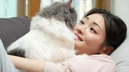 집에서 소파에 누워 고양이와 시간 보내는 젊은여자 모습