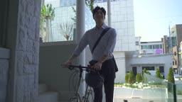스타트업비즈니스 자전거 끌고 출근하는 청년 모습