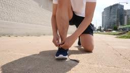 운동 도심 신발 끈을 묶는 젊은 남자 모습