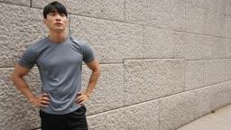 운동 도심 벽에 기대어 휴식을 취하는 젊은 남자 모습
