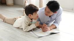 홈스쿨링 거실에서 아빠와 아들이 공부하는 모습