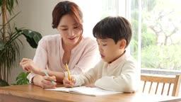 홈스쿨링 엄마와 아들이 책상에 앉아서 공부하는 모습