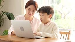 홈스쿨링 엄마와 아들이 책상에 앉아서 컴퓨터 학습하는 모습