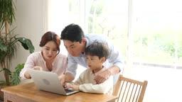 홈스쿨링 가족이 책상에 모여 컴퓨터 학습하는 모습