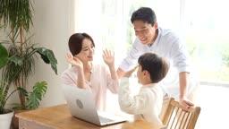 홈스쿨링 가족이 책상에 모여 컴퓨터 학습하며 하이파이브 하는 모습