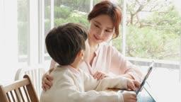 홈스쿨링 엄마와 아들이 책상에 앉아서 태블릿피씨로 학습하는 모습