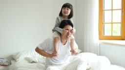 가족 침대에서 목마하며 까꿍놀이하는 아빠와 딸 모습
