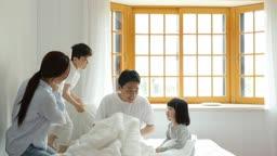 가족 침대에서 베개싸움하는 모습