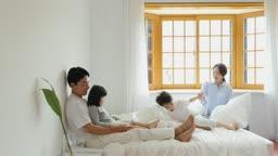가족 침대에서 베개로 장난치며 노는 모습