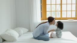 가족 침대에서 뽀뽀하는 엄마와 딸 모습
