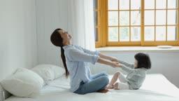 가족 침대에서 손잡고 노는 엄마와 딸 모습