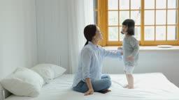 가족 침대에서 점프하며 노는 엄마와 딸 모습
