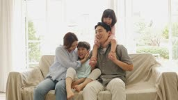 가족 소파에 앉아서 카메라 응시하는 모습