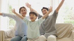 가족 소파에 앉아서 만세하는 모습
