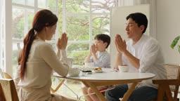 가족 식탁에서 식사 전 기도하는 모습