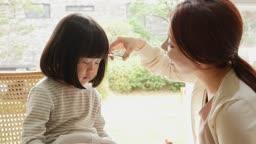 가족 거실에서 미용하는 엄마와 딸 모습