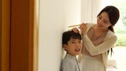 가족 거실에서 키재는 엄마와 아들 모습