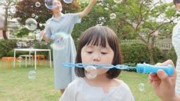 가족 집 정원에서 비눗방울 놀이 하는 모습