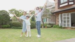 가족 집 정원에서 만세하며 카메라 응시하는 모습
