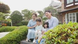가족 집 정원 계단에 앉아서 카메라 응시하는 모습
