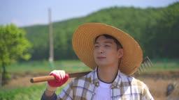 귀농귀촌 농사 농기구 들고 밭을 걷고 있는 청년 모습