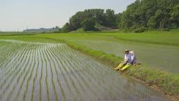 귀농귀촌 농사 밭에 앉아서 과일 들고 대화 나누고 있는 부부 모습