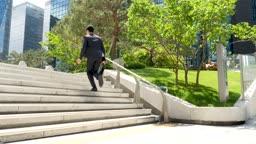 도심 계단을 뛰어오르는 비즈니스맨 모습