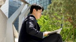 도심 계단에 앉아 노트북으로 업무보는 비즈니스맨 모습