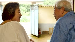 집에서 마주보며 대화 나누는 노부부 모습