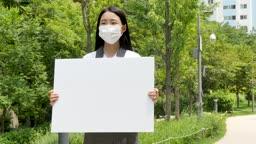마스크 끼고 화이트보드 들고 있는 교복을 입은 여학생 모습
