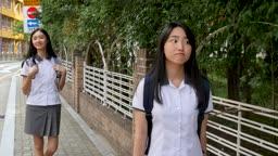 보도블록을 걷고 있는 교복을 입은 여학생들 모습