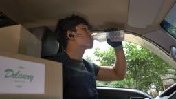 택배 배송 차량 안에서 물 마시는 택배기사