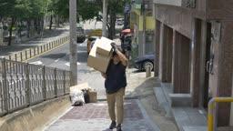 오르막길에서 택배 상자 옮기는 택배기사