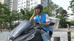 통화 후 오토바이로 이동하는 배달원