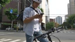 핸드폰으로 배송지 확인 후 자전거로 이동하는 배달원