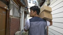 골목에서 택배 상자 들고 배송지 찾는 택배기사