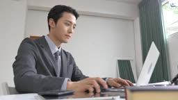 사무실에서 노트북 사용하여 일하는 남자 모습