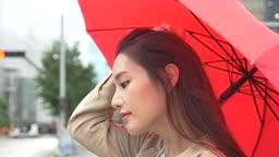 빨간 우산 쓰고 주위를 둘러보는 여자 모습