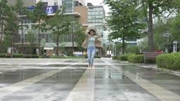 가방으로 비를 피하며 뛰어가는 여자 모습