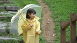 노란 우산과 우비 입고 걸어가는 여자아이 모습