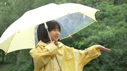 노란 우산과 우비 입고 손 내밀어 비를 만지는 여자아이 모습