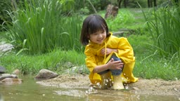 노란 우비와 장화 신고 물장난치는 여자아이 모습