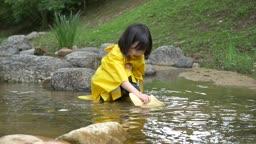 노란 우비 입고 장화에 물 담아 물장난치는 여자아이 모습