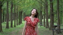 공원 숲길을 걸으며 주위를 둘러보는 여자 모습