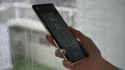 핸드폰 어플로 날씨 확인하는 모습