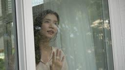 창문을 열고 손을 내밀어 비를 만지는 여자 모습