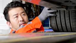 자동차 정비소 바퀴와 타이어 점검하는 정비사 모습
