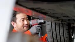 자동차 정비소 바퀴 너트 체결하는 정비사 모습