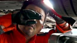 자동차 정비소 하부 점검하는 정비사 모습