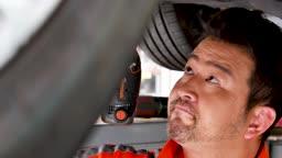 자동차 정비소 하부 너트 체결하는 정비사 모습